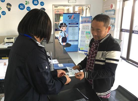 图为:民警将临时身份证交到张先生手中。 平湖警方 供图