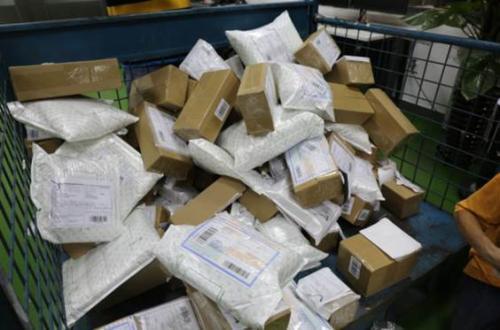 (图说:警方在广州白云机场国际物流中心查扣百余个即将发往国外的假货邮包。)