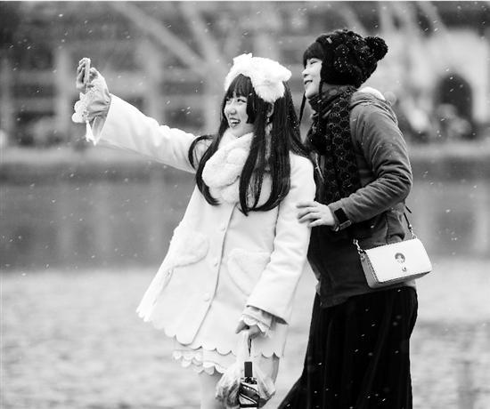 12月30日,追雪的游客来到西湖断桥景区。 记者 倪雁强 摄