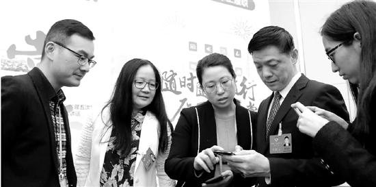 """省政协委员们在大会网络技术组工作人员的介绍下,了解并使用""""浙江政协·掌上履职""""平台。记者 吴煌 摄"""