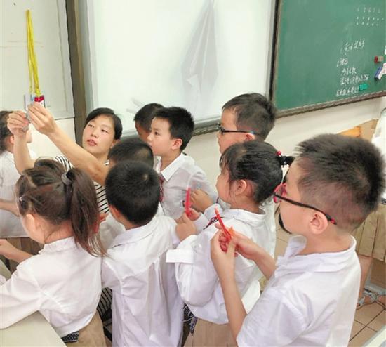 一年级学生在家长志愿者带领下学折纸。 浙江在线 图