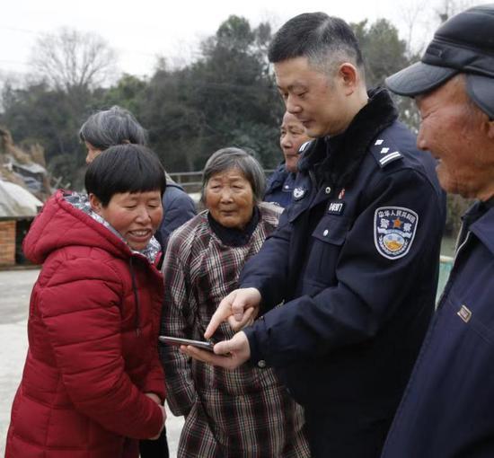 民警为杨通美展示贵州老家的视频资料。海盐警方供图