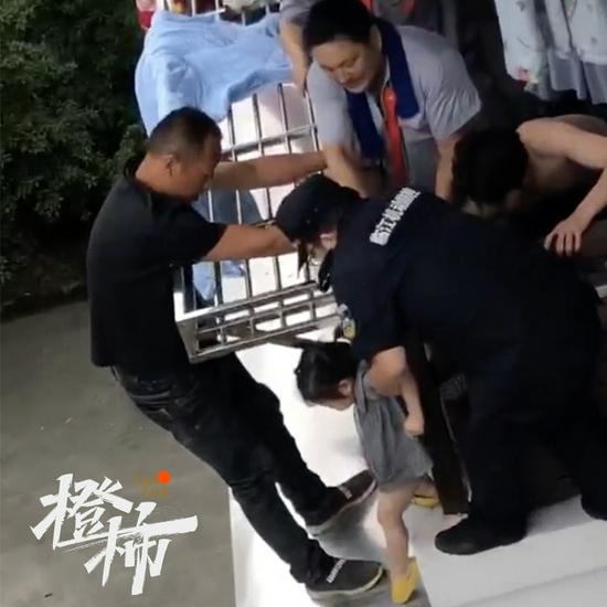 杭州一两岁女孩站在阳台外的雨棚上 居民合力救下