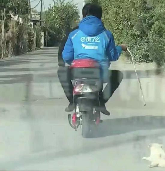 """穿""""饿了么""""工作服的男子在拖行小狗。 行车记录仪视频截图"""