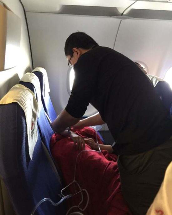 图为:台州市第一人民医院医生杨心宇在飞机上为女乘客进行应急处理。王璐曦 摄