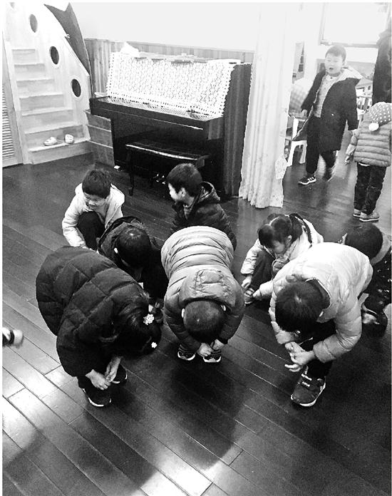 下图:幼儿园小朋友在学系鞋带。很多还不会蹲着系。