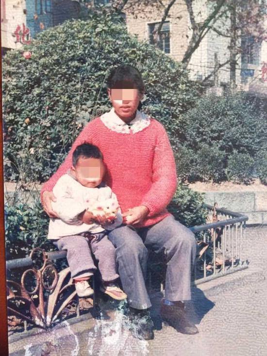(图:李雪随身携带着她与儿子幼时的合影)