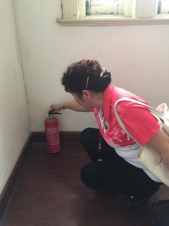 鲍建玲在查看历史建筑内部的灭火器。