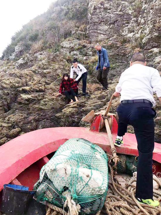 救援人员正在救助礁石上的船员妻子。余舟象 图