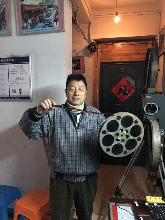 近日,杨志平在家中向记者演示如何组装老式放映机。
