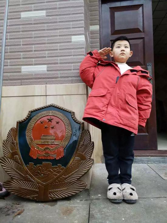 """图为:8岁""""警二代""""用压岁钱从废品站淘回一块旧警徽 玉环公安供图"""