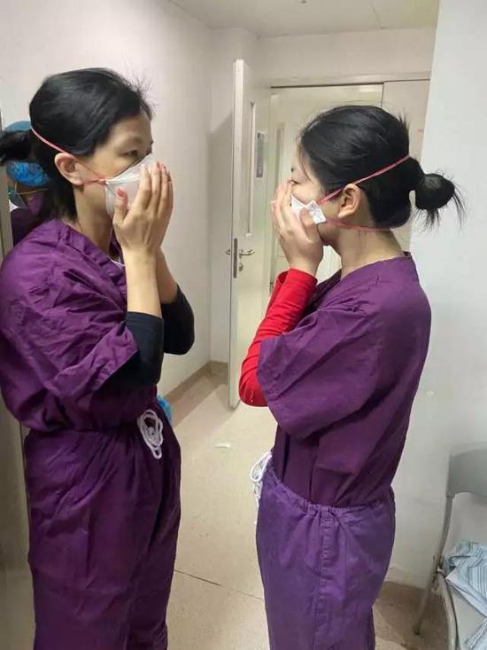 医务人员在清洁区相互检查口罩佩戴情况