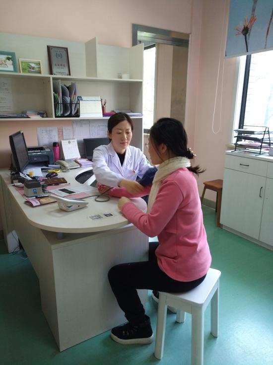 周丽丽科长在为建小卡孕妇量血压