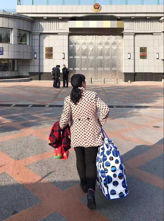 (图:李雪拎着的蛇皮袋里,装的都是给她儿子买的东西。)