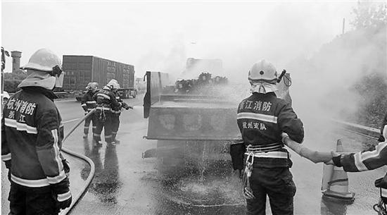 消防队员出动水枪对起火货车进行扑救