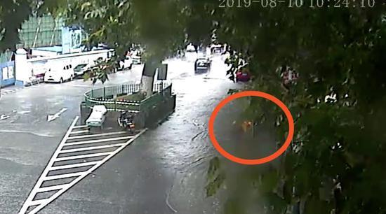 图为:台风天外卖小哥沿路徒手清理积水。磐安公安提供