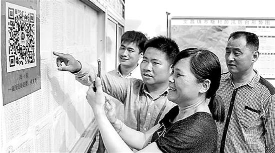 淳安县文昌镇监察办成员向群众推广微信举报平台。