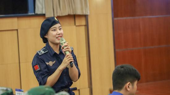 图为:杭州西湖女子巡逻队江会芳与同学们互动。邓漠鹏摄