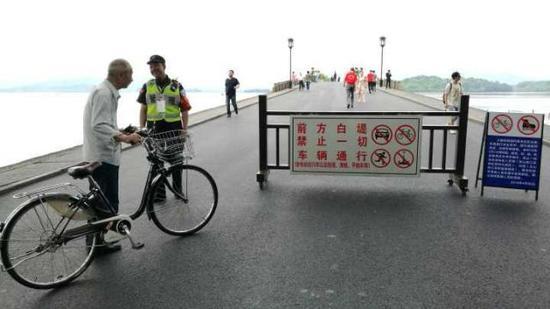 ▲白堤出口,断桥。今晨,岳庙管理处的保安正在劝阻非机动车进入白堤。