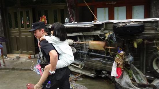永嘉特警队员背着受灾儿童,将其转移出灾区。 永嘉警方供图
