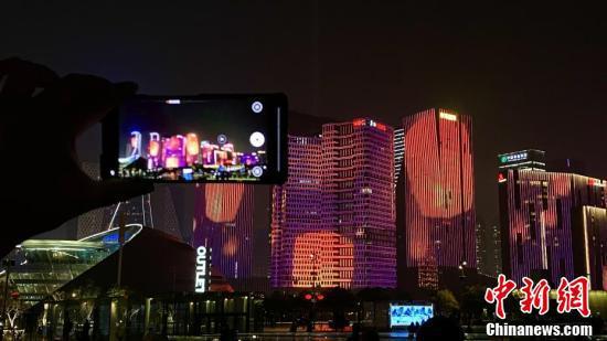 牛年贺岁版灯光秀在钱塘江畔上演 游人用手机拍摄