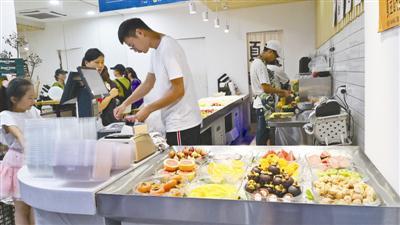 鲜切水果店受到年轻人青睐。