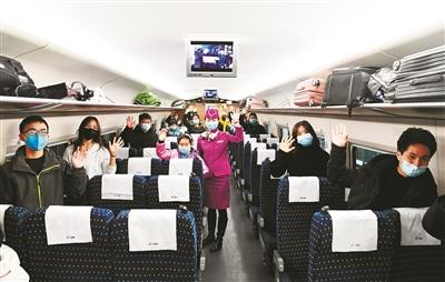 务工人员与列车员在G4138次返程专列上合影。 新华社发