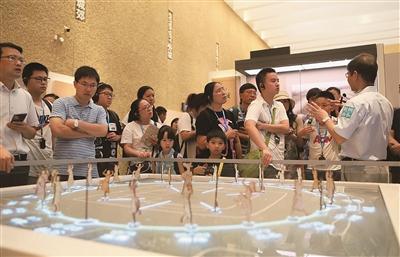 周新华(右)为市民讲解良渚文化知识