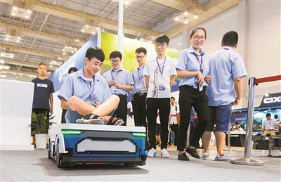 智博会上一家企业展出的AGV小车吸引了不少市民驻足。 (殷聪 摄)