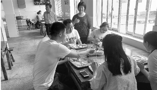 陈小美开心地看着老师们津津有味吃她做的小菜。