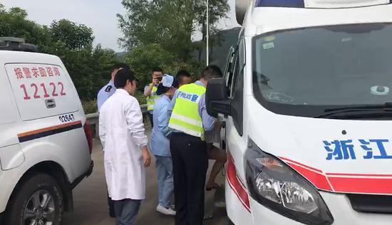 图为:民警护送事故中受伤的孕妇下高速 王颖俊 摄