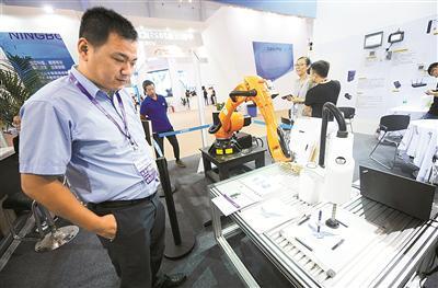 智博会上展出的六轴机器人正在展示绘图技术。 (殷聪 摄)