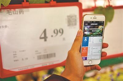 """手机扫取二维码,就可以了解菜品的""""前世今生""""。(徐展新 摄)"""