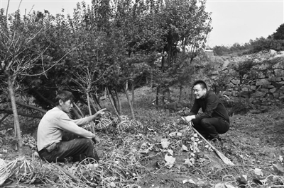 周荣江在回访已经搬迁的村民,了解他们的生活情况。 受访者供图