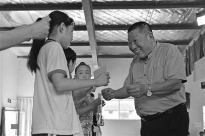 公式王立毅先生给孩子们发放广量教育基金。