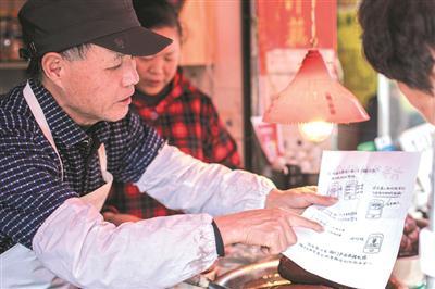 凤起路农贸市场卖蜜藕的摊主老方,教老年人上网买菜。