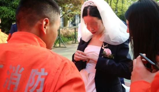 大家围着一位穿婚纱的年轻姑娘