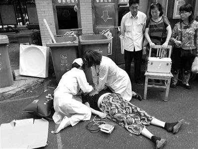 满医生跪在地上给大妈急救 图片由小区居民拍摄