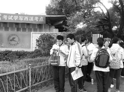 考前,考生在门口抓紧时间最后再看两道题。 首席记者 张娜 摄