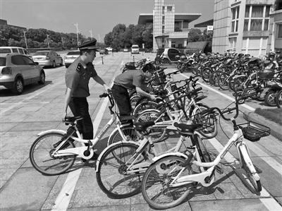 城管执法人员在清理街头乱停放的共享单车
