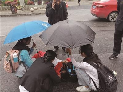 风华中学两位女生帮倒地男孩撑伞 学校供图