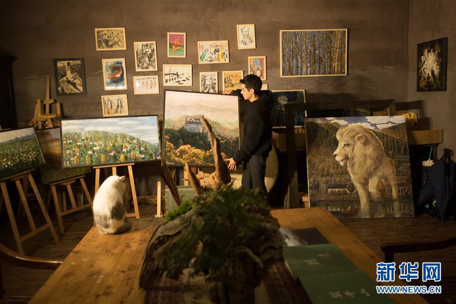 1月7日,旺仔在工作室内搬动作品,墙上悬挂的是他少年时期的创作。
