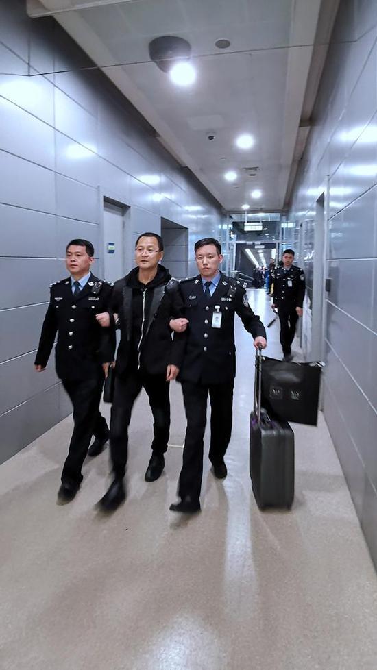 袁国方在机场边检人员的带领下离开飞机从登机口出来(胡高生 摄)
