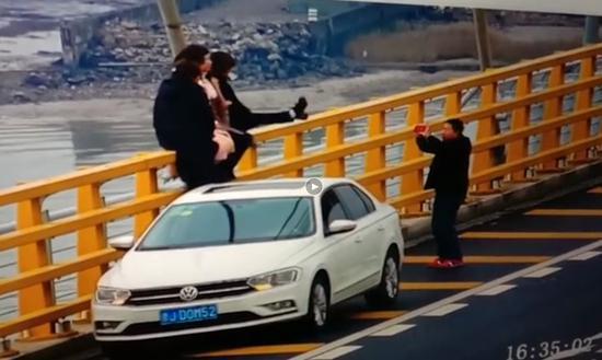图为:4名女子高速上停车攀爬拍照。高速交警台州支队供图