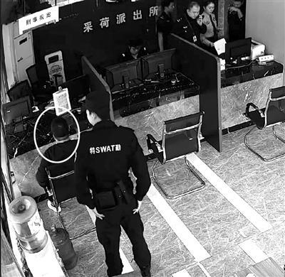 ②查出结果,协警站在他身后。