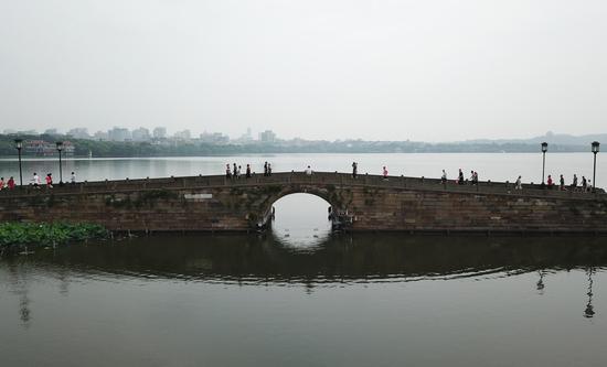 图为:市民游客在西湖断桥健身、游览(航拍)。王刚