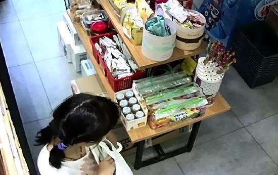 女孩把一包零食塞进包里。监控截图 由店铺徐老板提供