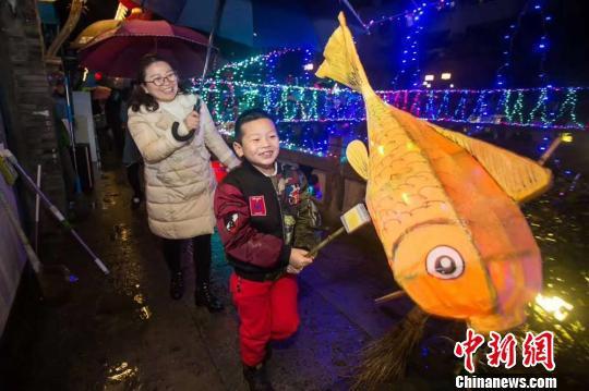 小朋友举着花灯与家人一起游街 王敏智 摄