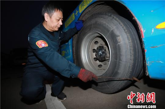 图为吴益君检查轮胎是否正常。 董美巧 摄