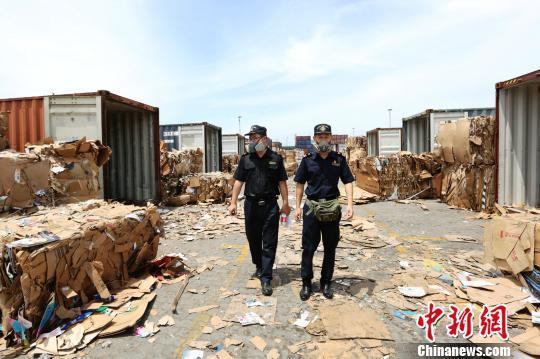 嘉兴海关关员穿梭在嘉兴港进境废纸查验场地上。嘉兴海关提供